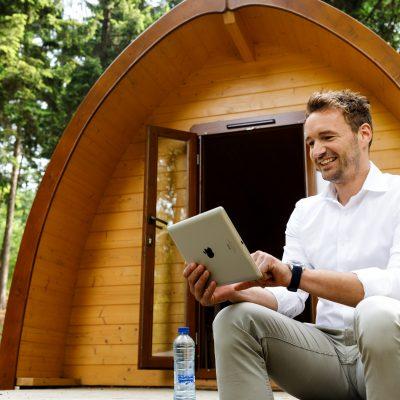 Een sfeerbeeld van een man die met een laptop voor een mini vakantiehuisje zit.